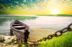 Barca alla costa contro il tramonto. Immagini Stock
