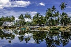 Barca ancorata, riflessione del pescatore su acqua fondo del ble e nuvoloso del cielo Immagine Stock Libera da Diritti