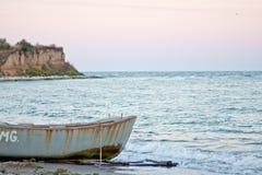 Barca arrugginita sulla riva, al tramonto Immagini Stock