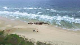 Barca arrugginita sulla riva con l'oceano e gli alberi archivi video