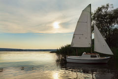 Barca attraccata con la vela al tramonto, lago Fotografia Stock Libera da Diritti