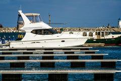 Barca bianca messa in bacino in porto marittimo Immagine Stock