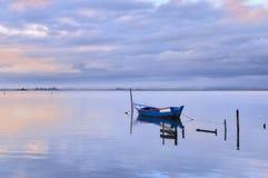 Barca blu da solo sulla laguna al tramonto fotografia stock libera da diritti