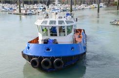 Barca blu del rimorchiatore in un porticciolo fotografia stock