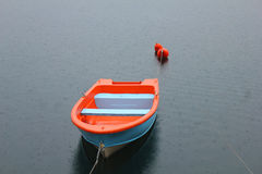 Barca blu ed arancio sul lago Fotografia Stock