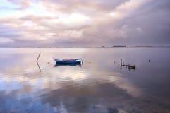 Barca blu in mezzo al lago nell'ambito del tramonto fotografia stock