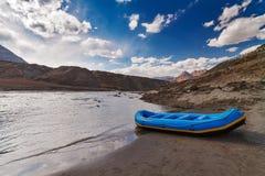 Barca blu nel fiume della montagna Fotografie Stock