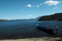 Barca blu nel lago Lugu fotografie stock