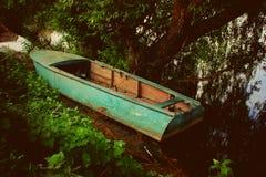 Barca blu nella tonalità di un albero dal fiume Fotografia Stock