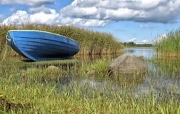 Barca blu sulla riva del lago nell'erba alta Immagini Stock Libere da Diritti