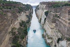 Barca in canale di Corinto sotto le nuvole pesanti fotografia stock libera da diritti