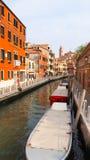 Barca in canale di Venezia con costruzione variopinta Fotografia Stock Libera da Diritti