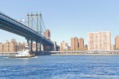 Barca che passa sotto il ponte di Manhattan a New York fotografia stock libera da diritti