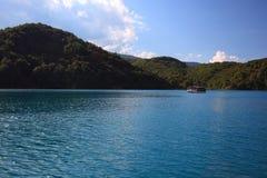 Barca con i passeggeri su un lago blu Fotografia Stock