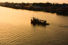 Barca con il tramonto in fiume Fotografia Stock