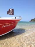 Barca con la bandiera di pirata tirata sull'isola Immagine Stock Libera da Diritti