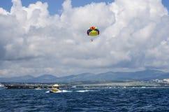 Barca con un paracadute di galleggiamento su una corda che va nel mare fotografia stock