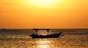 Barca del pescatore in Bali, Indonesia durante il tramonto dorato Oceano e cielo che assomigliano all'oro immagine stock