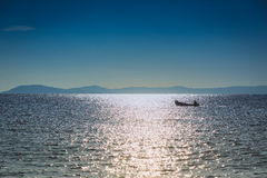 Barca del pescatore che galleggia nel mare su un fondo delle montagne Fotografie Stock