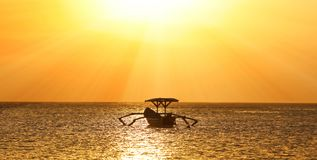 Barca del pescatore senza pescatore a Bali, Indonesia durante il tramonto alla spiaggia fotografia stock libera da diritti