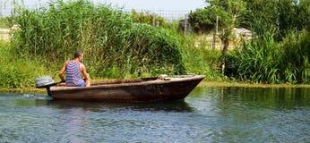 Barca dell'azionamento dell'uomo sul fiume fotografie stock libere da diritti