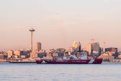 Barca della guardia costiera in Elliott Bay con il tramonto sopra i grattacieli del centro a Seattle, Washington, U.S.A. fotografia stock