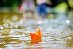Barca di carta arancio con una bandiera bianca Fotografia Stock Libera da Diritti