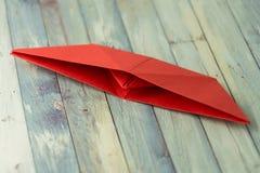 Barca di carta rossa caduta sulla tavola Iniziare un progetto/conclusione del concetto di estate Immagini Stock Libere da Diritti