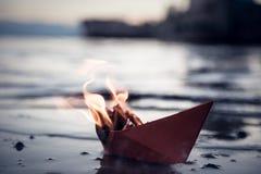 Barca di carta rossa su fuoco Immagini Stock