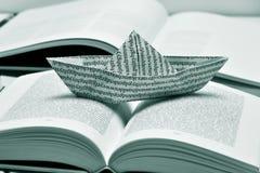 Barca di carta su un libro aperto, in bianco e nero Fotografie Stock
