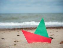 Barca di carta sulla spiaggia fotografia stock