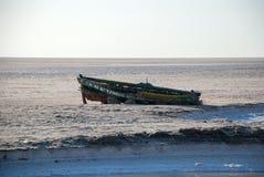 Barca di legno rotta sulla riva di un lago di sale Fotografie Stock