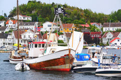 Barca di legno variopinta sull'acqua con una bandiera di pirata Immagine Stock Libera da Diritti