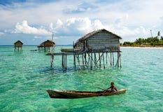 Barca di rematura del bambino del laut di Bajau vicino alla casa pomposa Immagini Stock