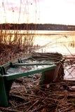 Barca distrutta sull'orlo di un lago Fotografie Stock