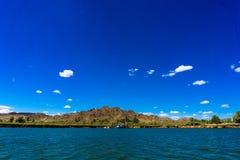 Barca do Rio Colorado e das montanhas e da dragagem sob o céu azul fotos de stock royalty free