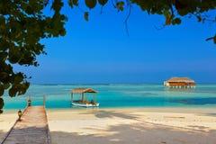 Barca e bungalow sull'isola delle Maldive Fotografie Stock