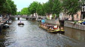 Barca facente un giro turistico nel canale di Amsterdam su una città di giorno soleggiato di Amsterdam archivi video
