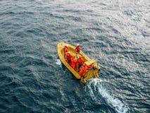 Barca gialla industriale con il gruppo di lavoratori irriconoscibili in tute uniformi arancio in acqua dell'oceano, vista aerea fotografie stock