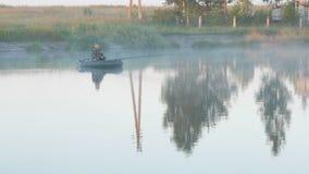Barca gonfiabile con un pescatore maschio su un lago nella nebbia Primo mattino video d archivio