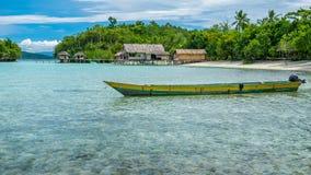 Barca locale della Papuasia, bello Lagoone blu vicino all'alloggio presso famiglie di Kordiris, alla piccola isola verde e a Home Immagine Stock Libera da Diritti