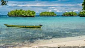 Barca locale della Papuasia, bello Lagoone blu vicino all'alloggio presso famiglie di Kordiris, piccola isola verde nel fondo, Ga Immagine Stock