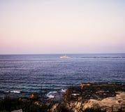 Barca lungo la costa nel tramonto Immagini Stock Libere da Diritti