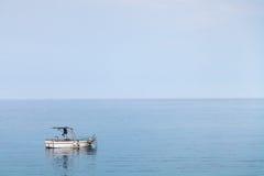 Barca in mare ionico nella penombra blu di sera immagine stock libera da diritti
