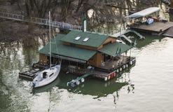 Barca messa in bacino alla casa di legno su Danubio immagini stock libere da diritti