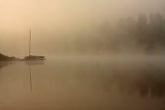 Barca nebbiosa di mattina nel lago Immagini Stock
