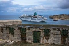 Barca nel porto di La Valletta al crepuscolo, Malta, Europa Immagine Stock