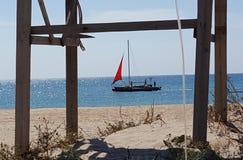 Barca nell'ambito del color scarlatto della vela al mare immagini stock libere da diritti