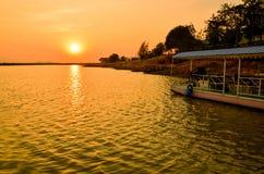 Barca in palude con il fondo di tramonto in Tailandia immagini stock libere da diritti