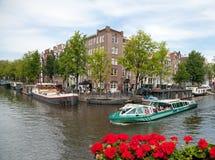 Barca in pieno della gente che passa un canale a Amsterdam con le vecchie costruzioni residenziali accanto  Immagine Stock
